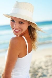 Portrait of a cute young couple with a straw hat at the beach